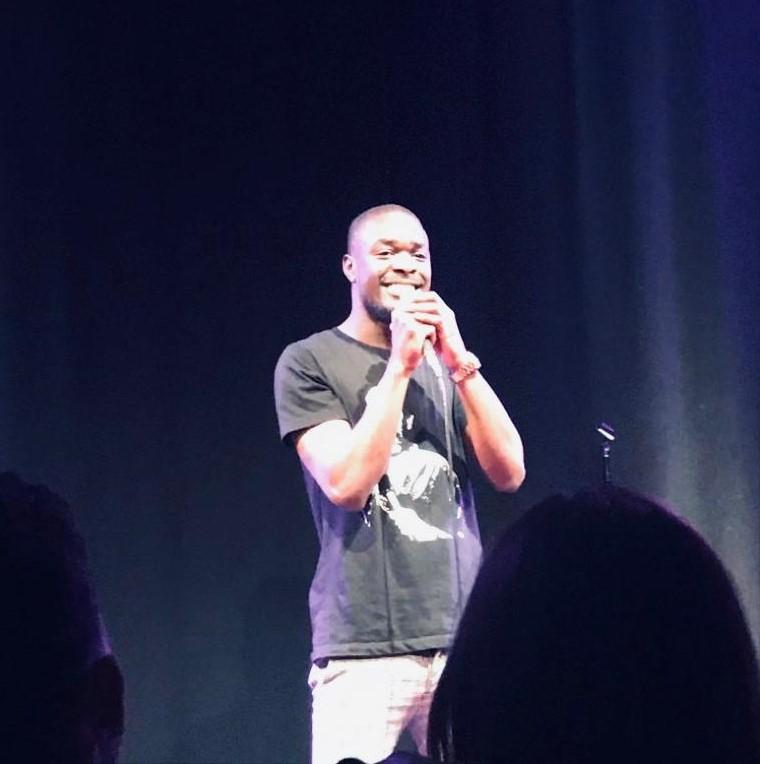 Nelson T Gombakomba Jr on stage holding a mic